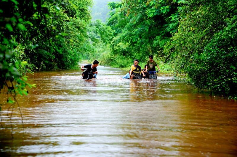 Grupp av lantliga barn som spelar i vatten, genom att rida cykeln royaltyfria bilder