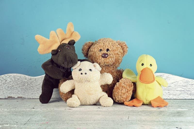 Grupp av leksaker för välfyllt djur på den vita trätabellen, djur royaltyfri fotografi