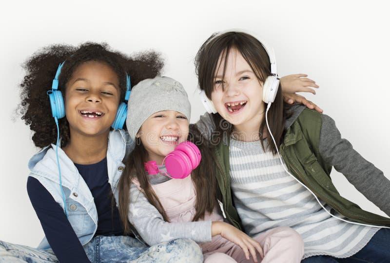 Grupp av liten flickastudion som ler bärande hörlurar och Wint royaltyfri fotografi