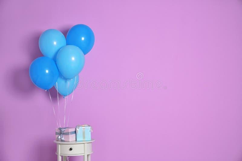 Grupp av ljusa ballonger och gåvor på tabellen royaltyfri foto