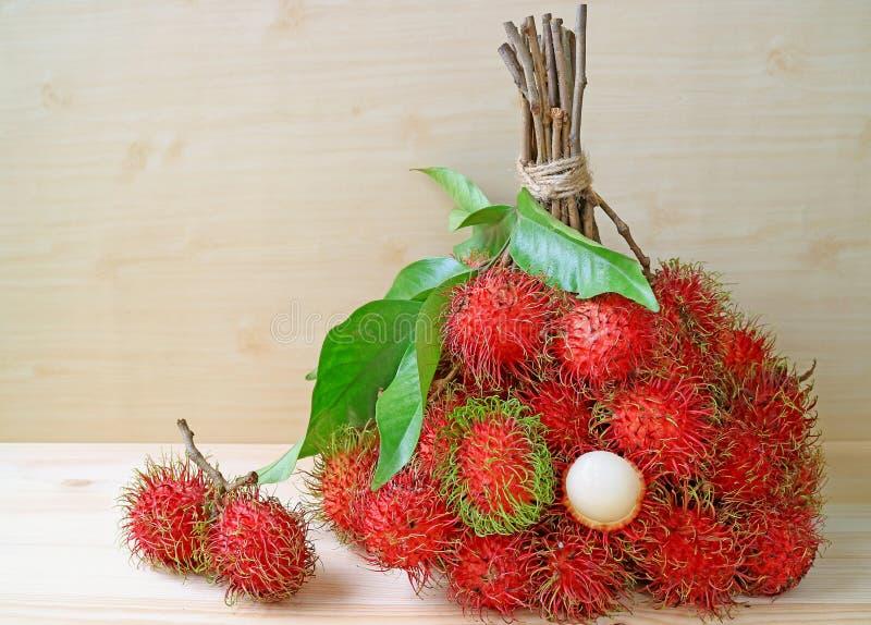 Grupp av ljusa frukter för röd och grön ny mogen Rambutan för färg hela och skalat isolerat på trätabellen royaltyfri foto