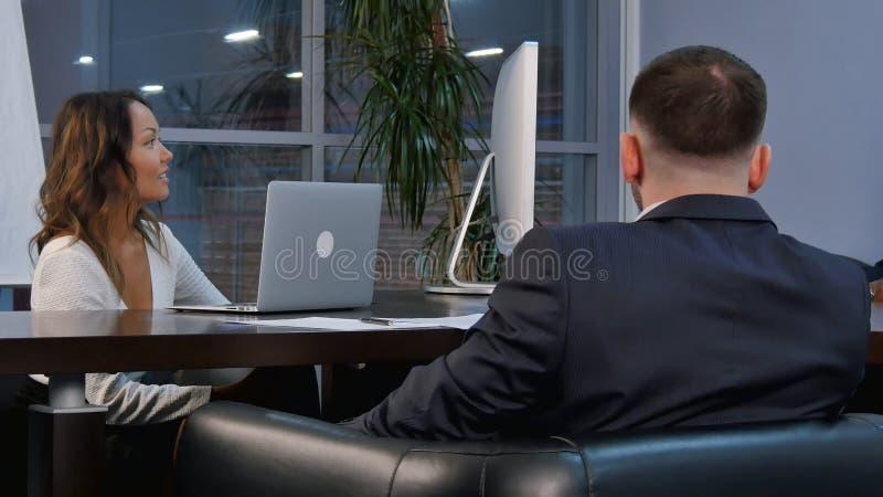 Grupp av lyckade businesspeople som tillsammans talar, medan arbeta runt om en tabell i en kontorsstyrelse arkivbilder