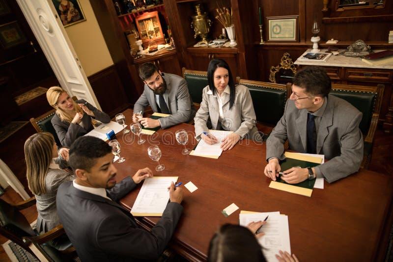 Grupp av lyckat affärsmanfolk i ett möte i regeringsställning arkivfoto