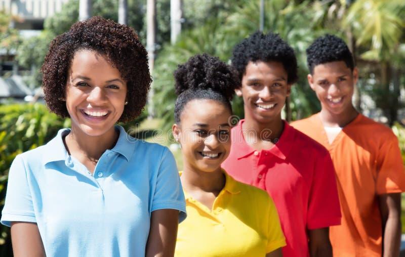 Grupp av lycklig latin fyra - amerikansk ung vuxen människa i linje arkivfoton