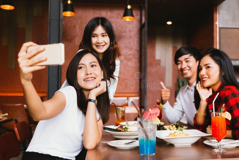 Grupp av lyckliga asiatiska manliga och kvinnliga vänner som tar ett selfiefoto royaltyfria foton
