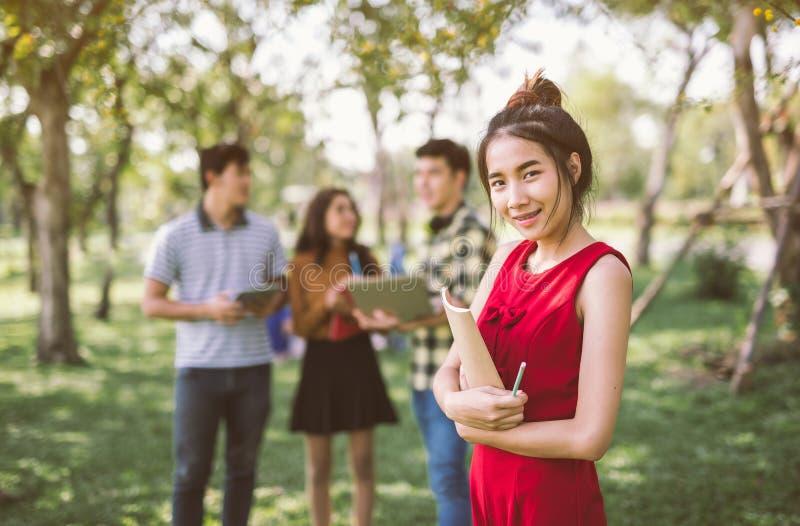 Grupp av lyckliga asiatiska tonårs- studenter med skolamappar royaltyfri foto