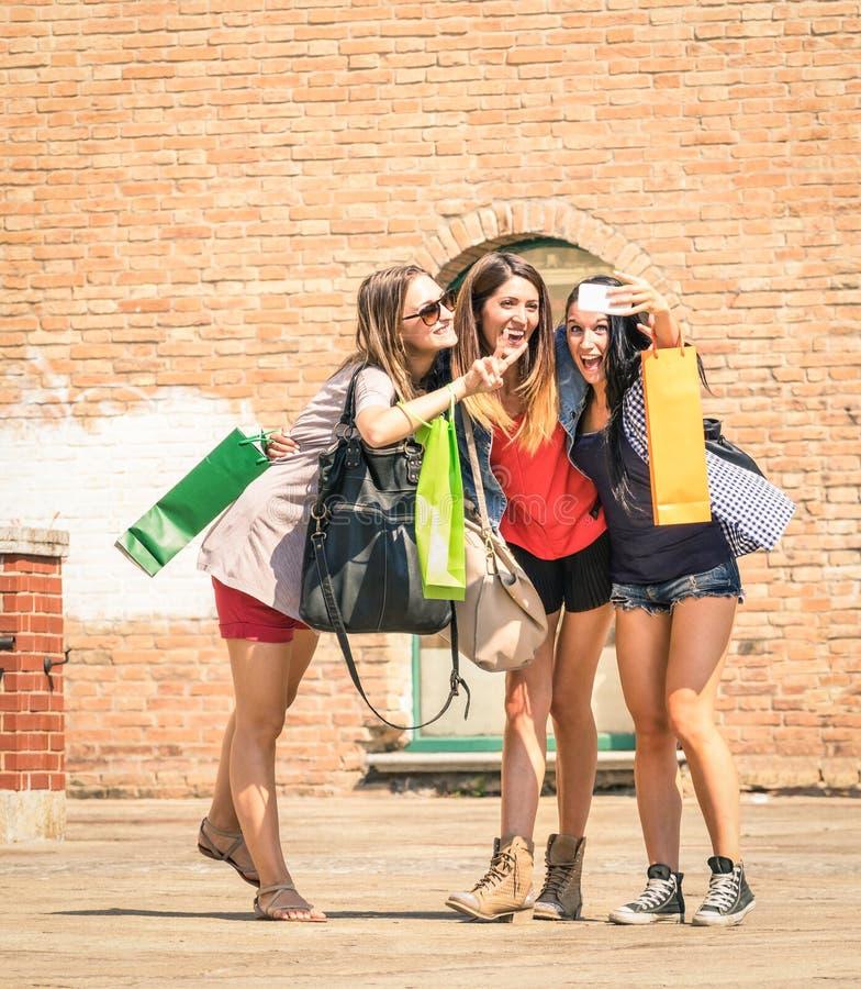 Grupp av lyckliga bästa vän med shoppingpåsar som tar en selfie royaltyfria foton