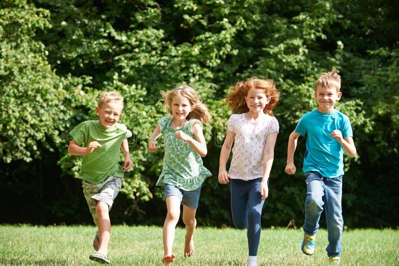Grupp av lyckliga barn som kör in mot kamera till och med fält arkivfoton