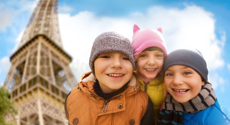 Grupp av lyckliga barn som kramar över Eiffeltorn arkivfoton