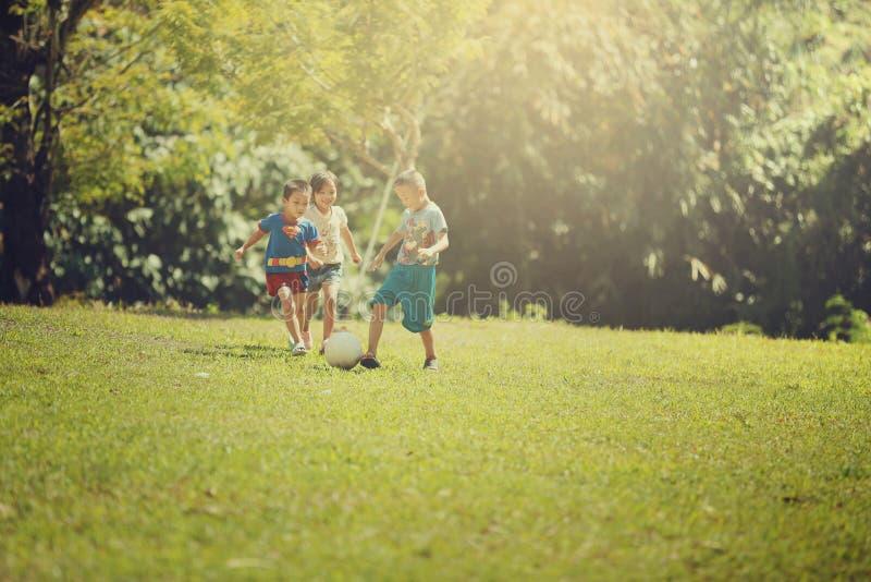Grupp av lyckliga barn som spelar med fotbollbollen royaltyfri foto