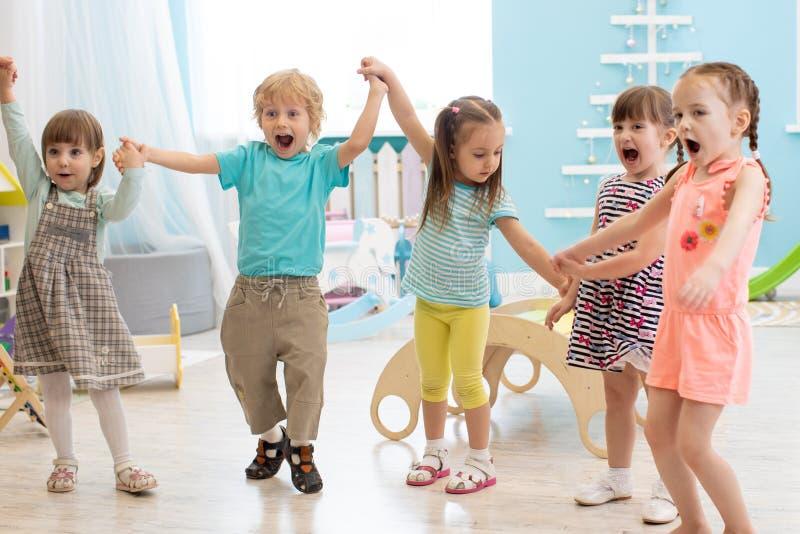 Grupp av lyckliga dagisungar som hoppar lyfta händer, medan ha gyckel i underhållningmitt arkivfoto