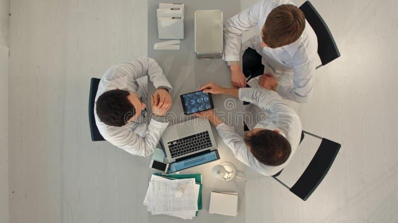 Grupp av lyckliga doktorer med minnestavlaPCdatorer som möter på det medicinska kontoret Top beskådar arkivbilder