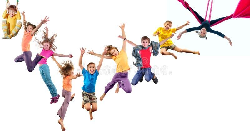Grupp av lyckliga gladlynta sportive barn som hoppar och dansar arkivbilder