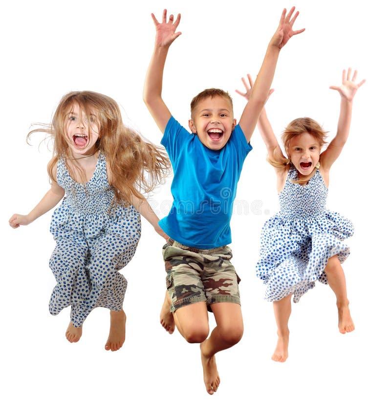Grupp av lyckliga gladlynta sportive barn som hoppar och dansar arkivbild