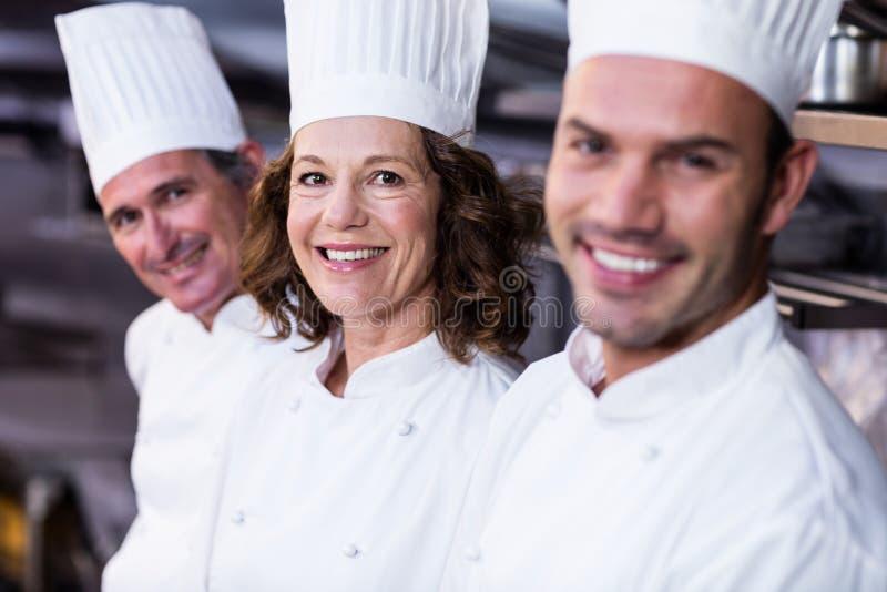 Grupp av lyckliga kockar som ler på kameran arkivfoton