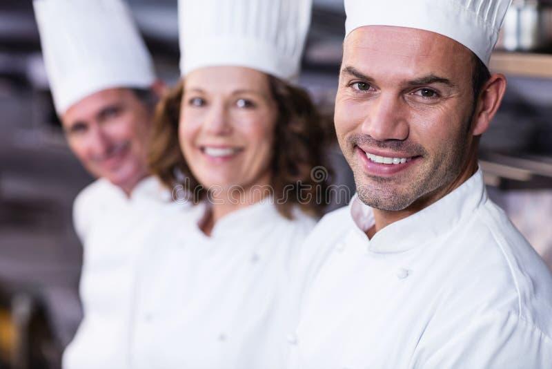 Grupp av lyckliga kockar som ler på kameran arkivfoto