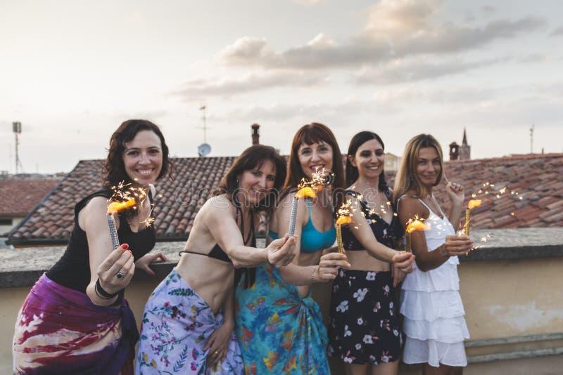 Grupp av lyckliga kvinnliga vänner som rymmer tomtebloss på takpartiet fotografering för bildbyråer