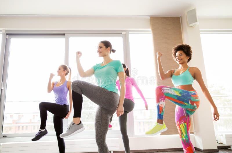 Grupp av lyckliga kvinnor som utarbetar i idrottshall fotografering för bildbyråer