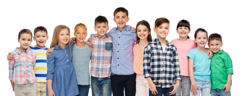 Grupp av lyckliga le barn som kramar över vit arkivfoton