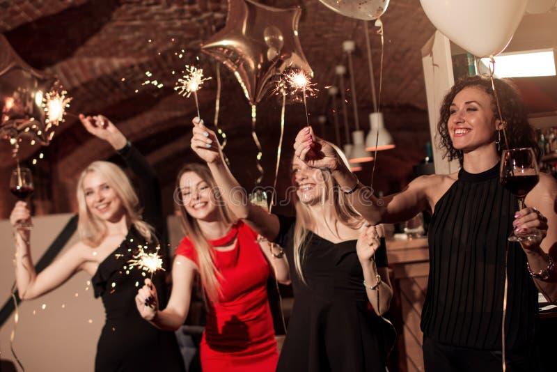 Grupp av lyckliga le flickvänner som bär aftonklänningar som firar hållande tomtebloss för nytt år i dekorerat kafé arkivbilder