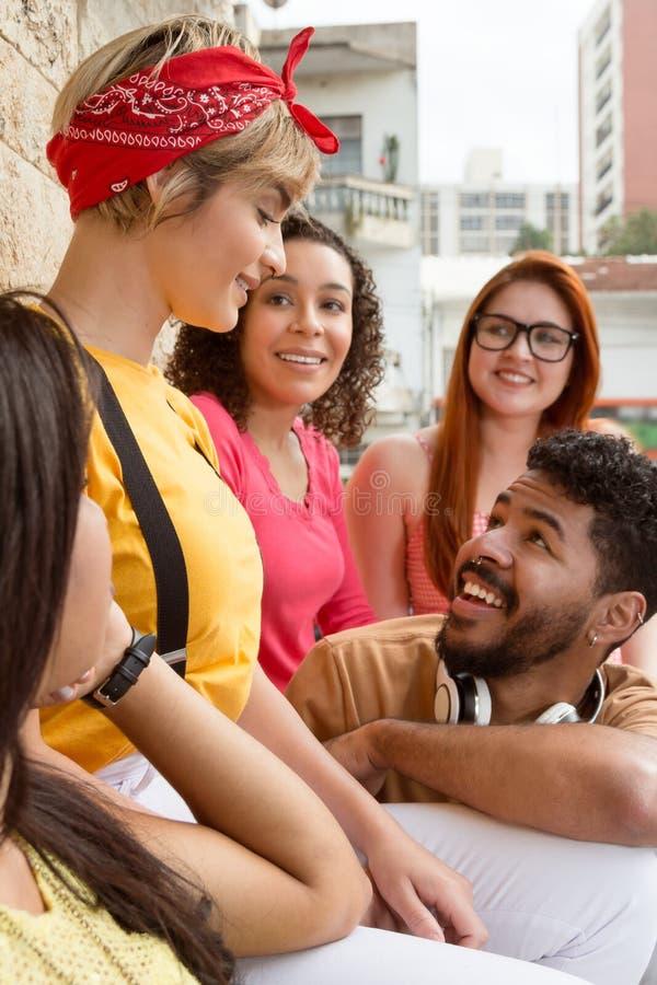 Grupp av lyckliga le studenter som har en stor tid på kaféstången arkivbilder