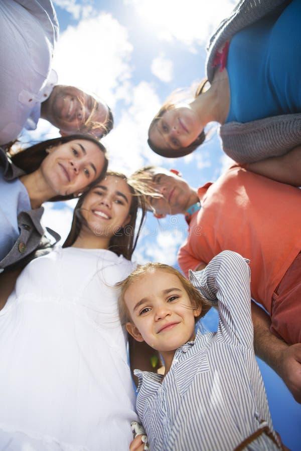 Grupp av lyckliga le vänner mot blå himmel arkivfoto