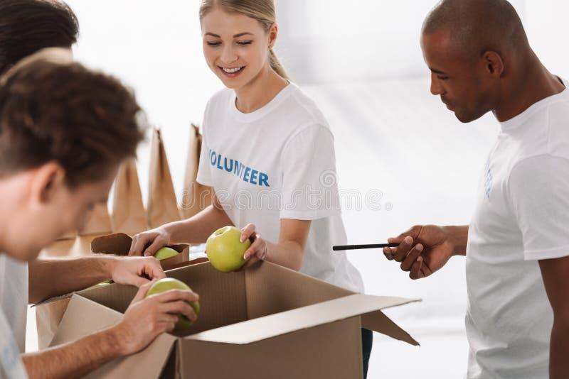 grupp av lyckliga multietniska volontärer som packar mat royaltyfria foton