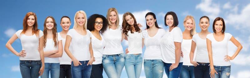 Grupp av lyckliga olika kvinnor i vita t-skjortor arkivfoto