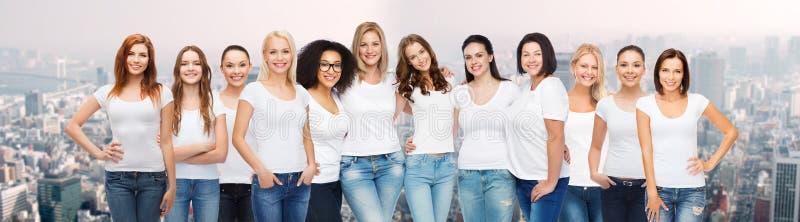Grupp av lyckliga olika kvinnor i vita t-skjortor royaltyfri bild