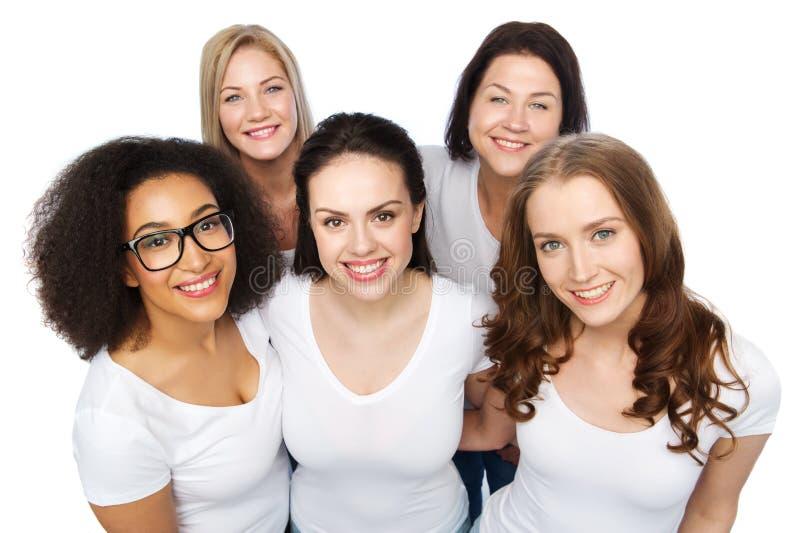 Grupp av lyckliga olika kvinnor i vita t-skjortor arkivbild