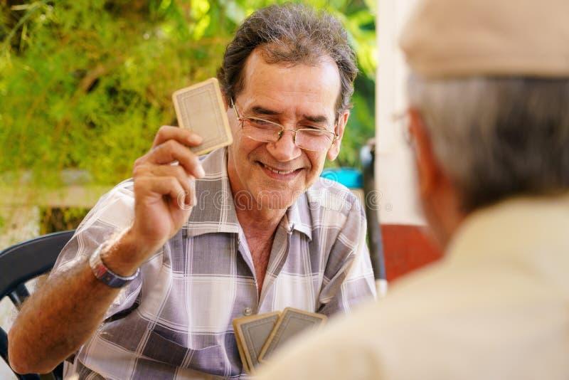 Grupp av lyckliga pensionärer som spelar kort och att skratta fotografering för bildbyråer