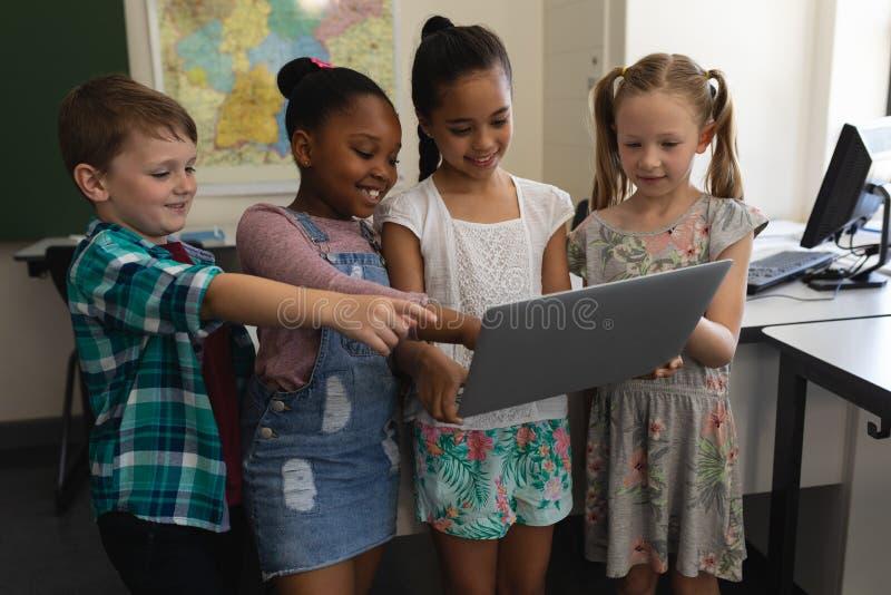 Grupp av lyckliga skolbarn som studerar på bärbara datorn i klassrum arkivbilder