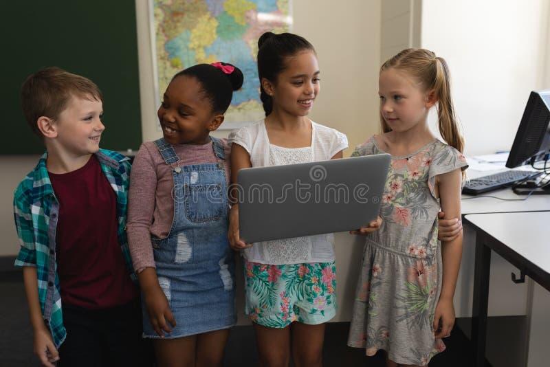 Grupp av lyckliga skolbarn som studerar på bärbara datorn i klassrum arkivfoto