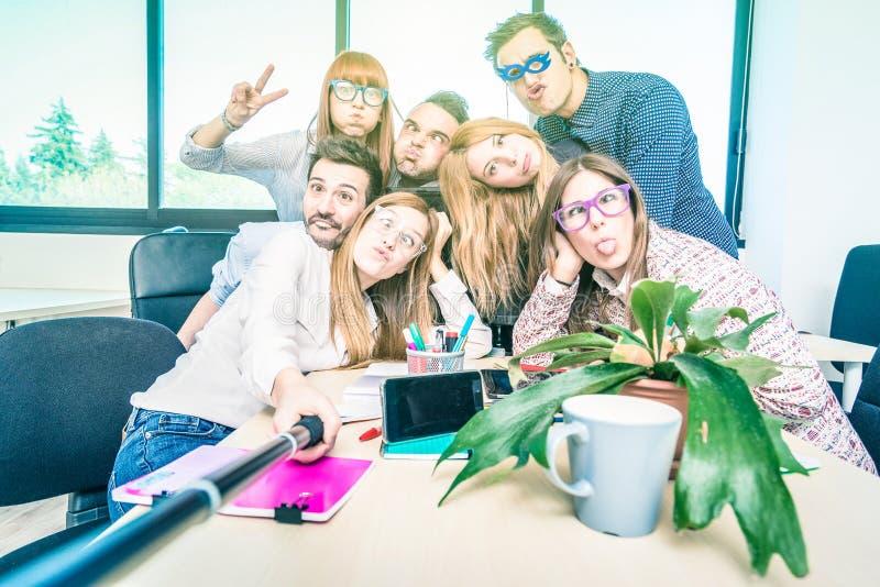 Grupp av lyckliga studentanställdarbetare som tar selfie royaltyfri bild