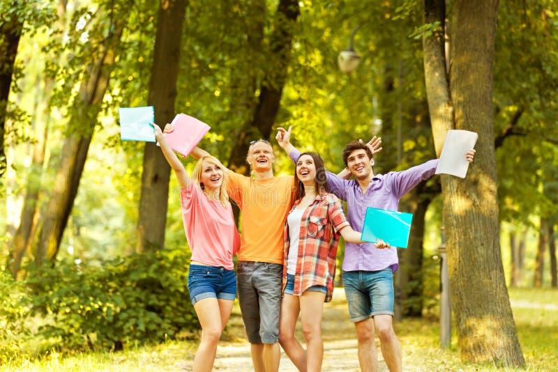 Grupp av lyckliga studenter med böcker i parkera royaltyfri fotografi