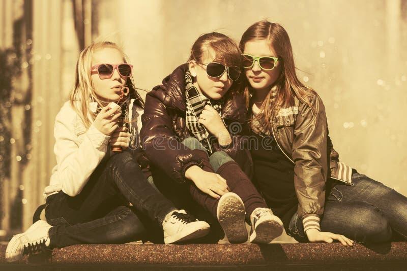 Grupp av lyckliga tonåriga flickor i stadsgata royaltyfri bild