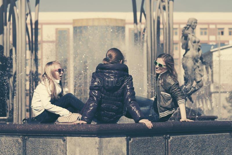 Grupp av lyckliga tonåriga flickor i stadsgata arkivfoto