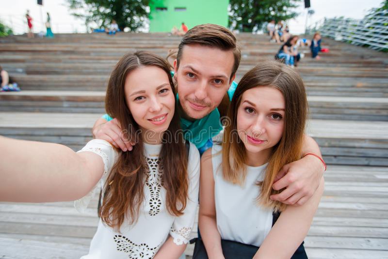 Grupp av lyckliga tonåriga vänner som skrattar och tar en selfie i gatan Tre vänner som håller ögonen på ta bilder med royaltyfri bild