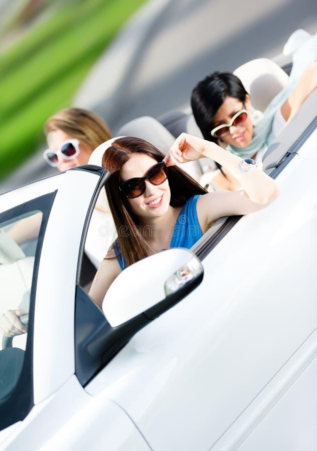 Grupp av lyckliga tonåringar i bilen arkivbilder