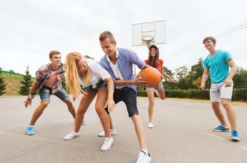 Grupp av lyckliga tonåringar som spelar basket royaltyfri foto