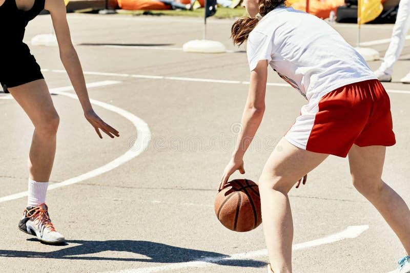 Grupp av lyckliga tonåringar som utomhus spelar basket arkivfoton