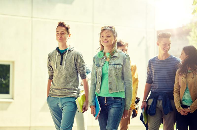 Grupp av lyckliga tonårs- studenter som utomhus går royaltyfria foton