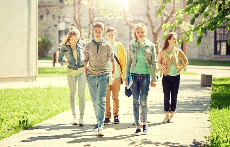 Grupp av lyckliga tonårs- studenter som utomhus går royaltyfri foto