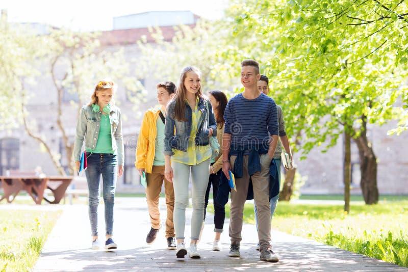 Grupp av lyckliga tonårs- studenter som utomhus går royaltyfri fotografi