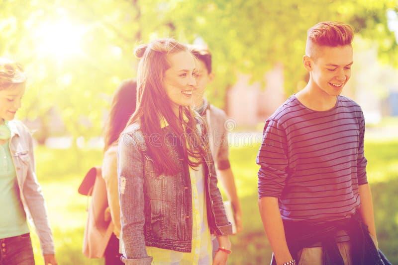 Grupp av lyckliga tonårs- studenter som utomhus går arkivfoton
