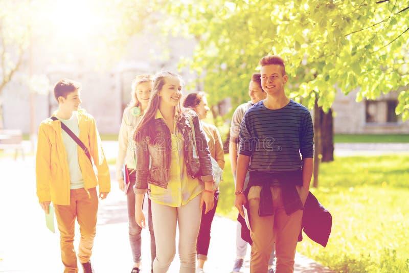 Grupp av lyckliga tonårs- studenter som utomhus går royaltyfri bild