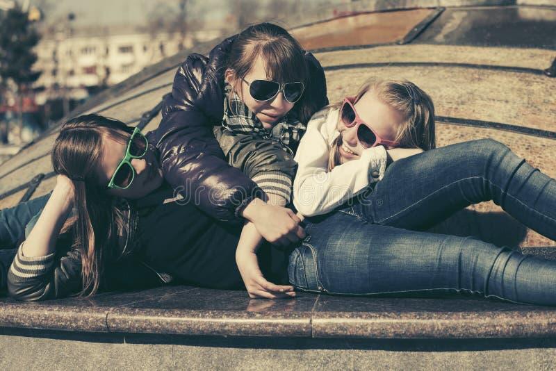 Grupp av lyckliga ton?riga flickor p? stadsgatan arkivfoton