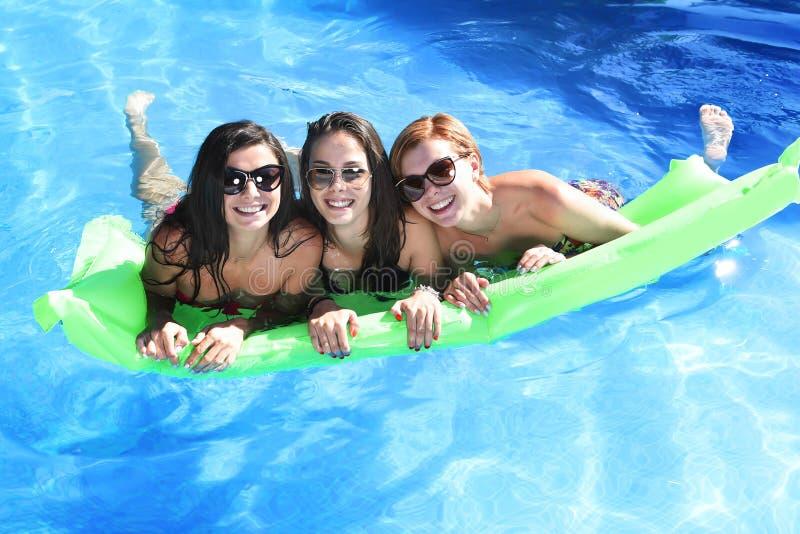 Grupp av lyckliga tre och härliga ung flickavänner som har slagträet royaltyfria foton