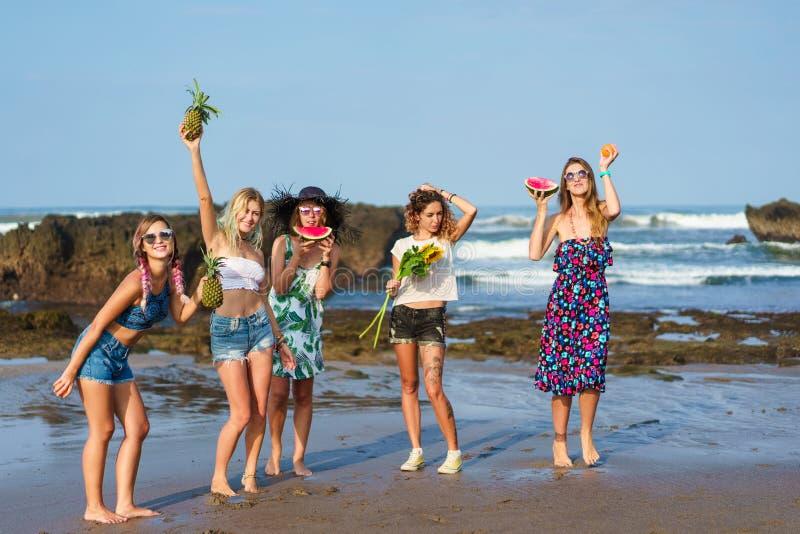 grupp av lyckliga unga kvinnor som rymmer olika frukter arkivbild