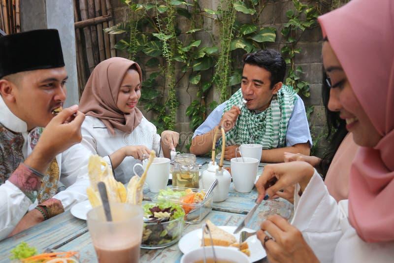 Grupp av lyckliga unga muslim som har matställen som är utomhus- under ramadan royaltyfri bild